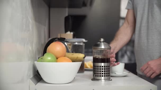 Man Pouring Coffee Into Cup At Modern Kitchen