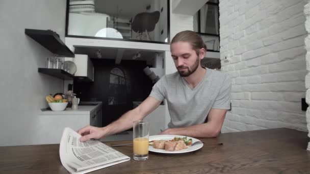 Man Reading Newspaper And Having Breakfast At Home In Kitchen