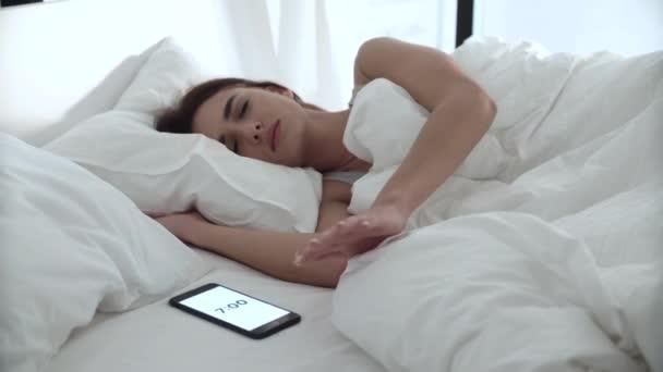 Budík na telefonu. Žena spí v posteli s bílým ložním prádlem
