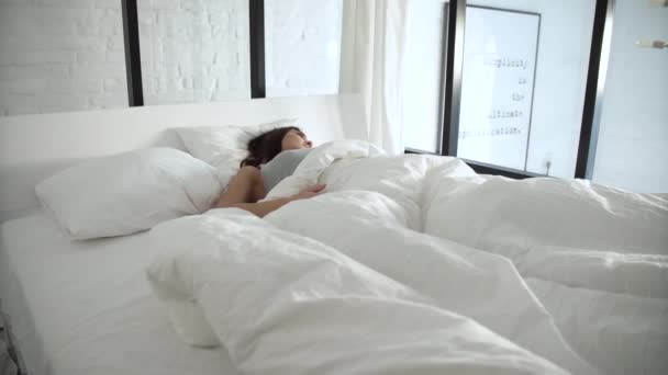 Woman Waking Up In Bed In Light Bedroom