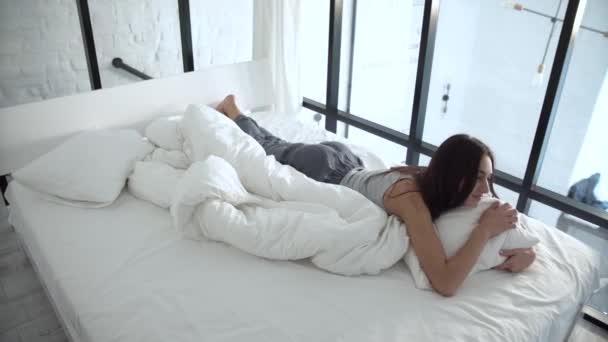 Krásná žena na pohodlné posteli ležel a objímala polštář