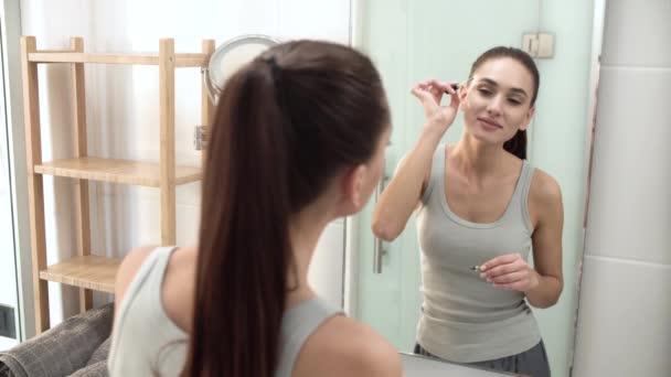 Beauty Makeup. Woman Brushing Eyebrows At Bathroom Mirror