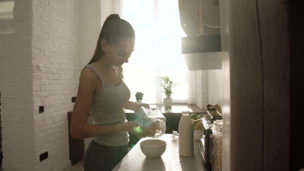 Frau kocht Flocken mit Milch zum Frühstück in leichter Küche
