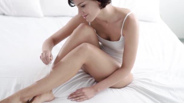 Péče o tělo. Žena nohy kůže dotýká s pérem