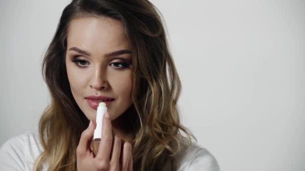 Péče o pleť rtů. Žena s použitím balzámu na rty make-up Beauty