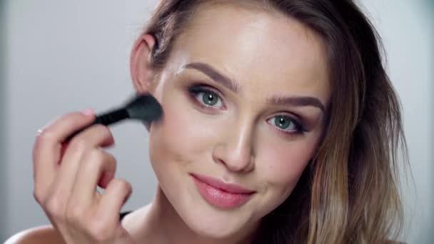 Žena s tváří kosmetické použití ruměnec make-up pomocí štětce