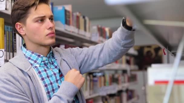 Student At Library. Man Looking Books On Bookshelves