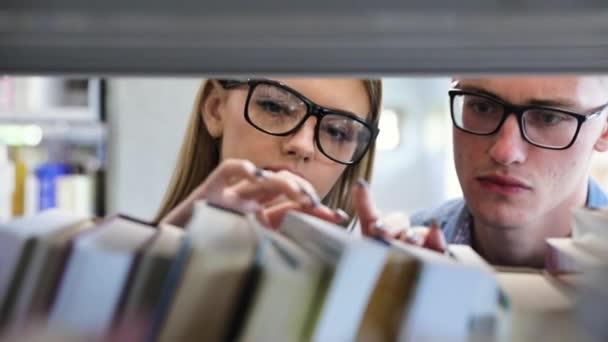 Studenti v knihovně hledání učení knihy na policích