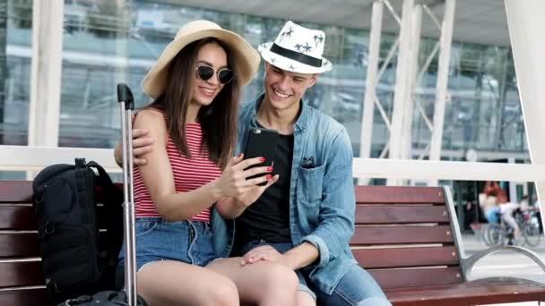 Cestování. Pár pomocí telefonu a sedící poblíž terminálu letiště