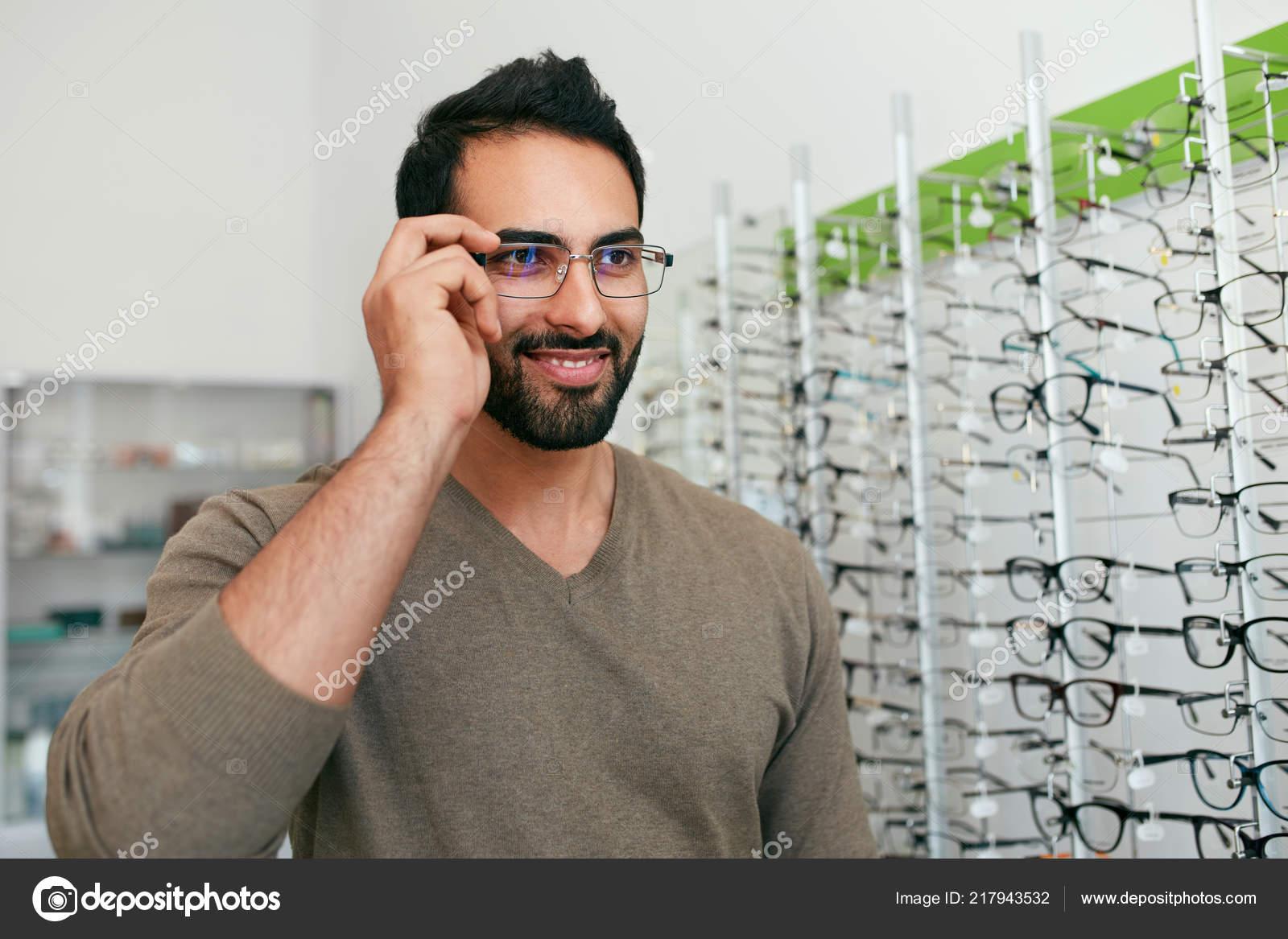 Loja de óculos. Homem experimenta óculos em loja de óptica — Fotografia de  Stock 711d036902