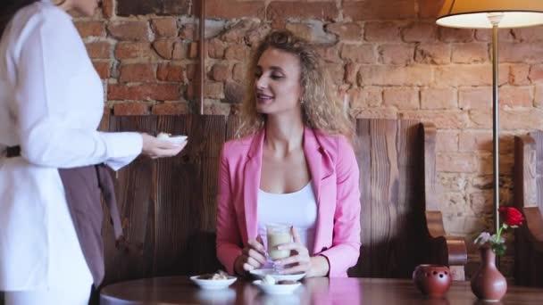 Žena v Cafe pití kávy s bonbóny, servírka obsluhující klientku