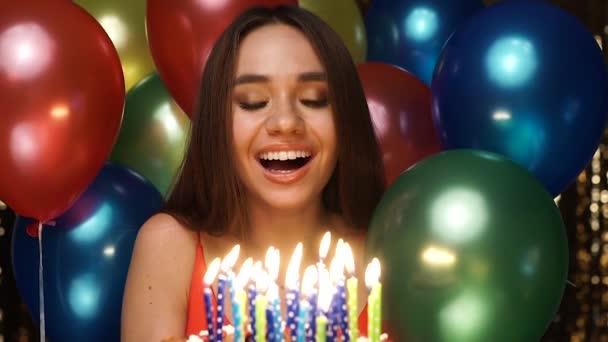 Narozeniny. Žena foukání svíčky na dort s balonky na Party