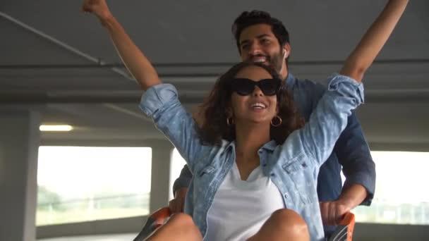 Šťastný pár se baví s nákupním košíkem na Mall parkování