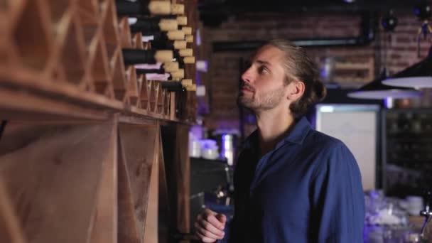 Víno Restaurant. Pohledný muž volba láhev vína na polici
