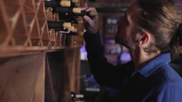 Ristorante di vino. Uomo bello scegliere la bottiglia di vino sullo scaffale