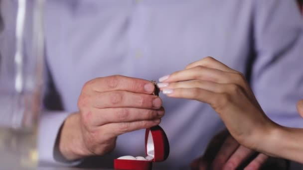 Marriage Proposal. Closeup Man Wearing Engagement Ring On Womans Hand In Restaurant