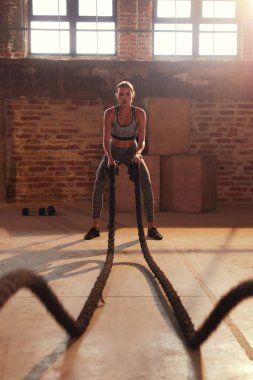 Fitness workout. Sport woman doing battle rope exercise at gym