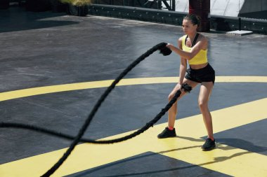 Sport woman doing battle ropes exercise workout at gym