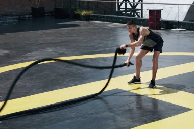 Sport man doing battle ropes exercise workout at gym outdoors