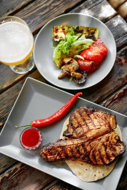 Steak And Beer. Barbecue Meat With Grill Vegetables And Beer