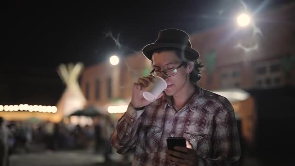 Young Man Drinking Coffee And Using Phone At Street In Evening
