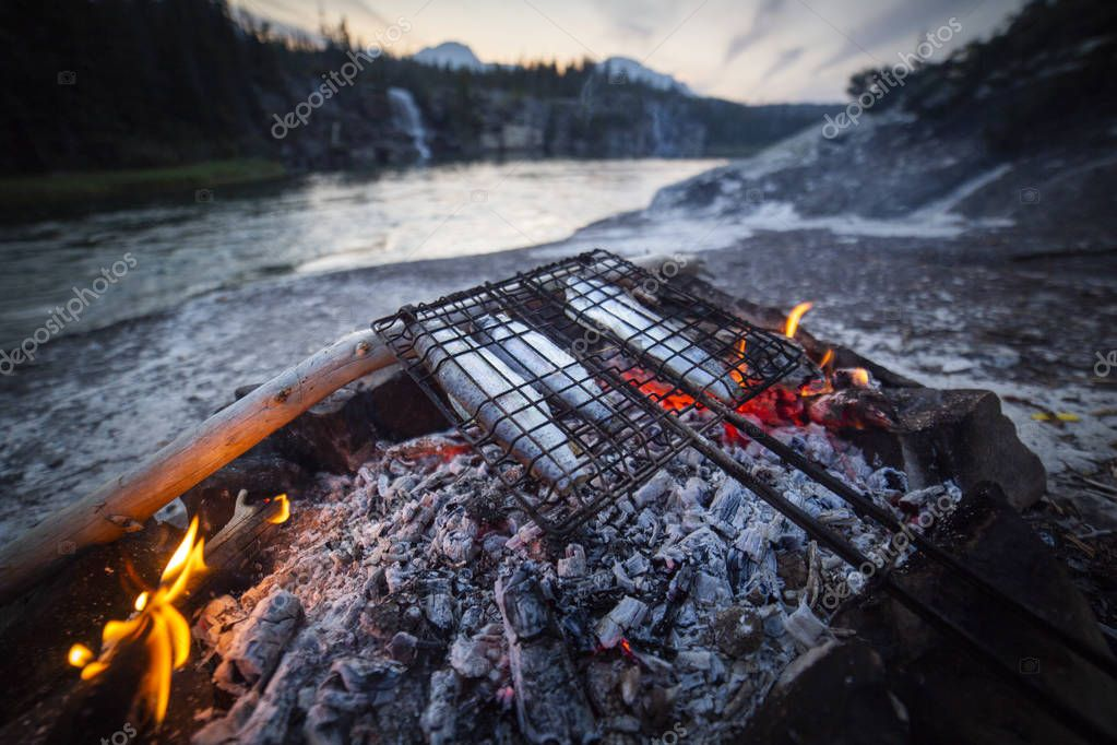 Fish cooking on grid with bonfire