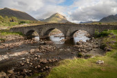Photo Old stone arch bridge over a mountain river at Sligachan on the Isle of Skye in the Highlands of Scotland, the Cuillin mountains rising behind lit by sunset