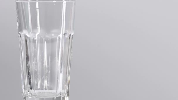 Vodní bubliny ve skle se pohybují nahoru. Vodní sklo izolované na bílém pozadí s malými bublinami.