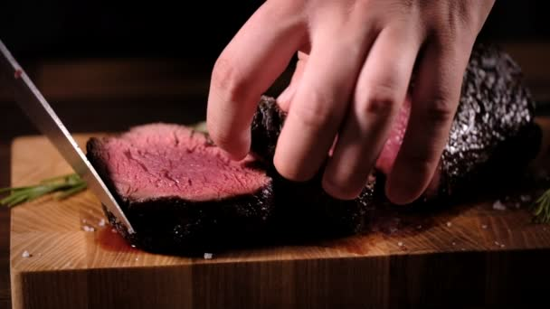 Cooking beef steak recipe - raw beef fillet in chef hands on cooking wooden table with herbs, salt and spices.