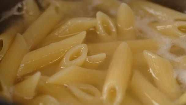 Close view of boiling penne pasta in saucepan