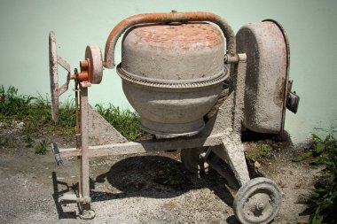 Dirty mini cement mixer in the the ground with little rocks and stones , tall green grasses behind it. Newly used equipment to build, fix structure put at the side of the house after done.