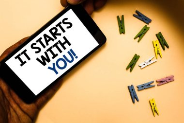 Conceptual hand writing showing It Starts With You. Business photo text Motivation for starting doing something Have discipline Hand holding iPhone with letters and paperclip peach color ground