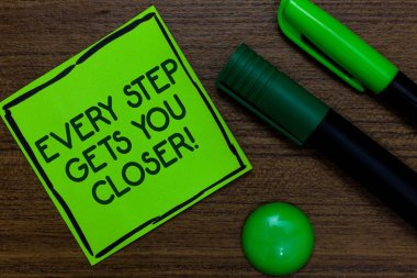 Text sign showing Every Step Gets You Closer. Conceptual photo Keep moving to reach your goals objectives Written on sticky note two markers laid on wooden floor green ball