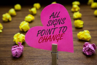 Text sign showing All Signs Point To Change. Conceptual photo Necessity of doing things differently new vision Paperclip hold pink heart with text blurry paper lobs on wooden floor