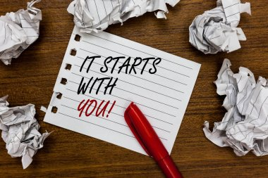Conceptual hand writing showing It Starts With You. Business photo showcasing Motivation for starting doing something Have discipline Written white page touched red marker scattered paper lump