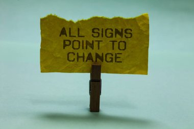 Text sign showing All Signs Point To Change. Conceptual photo Necessity of doing things differently new vision Paperclip hold torn yellow page written brown words sky blue background