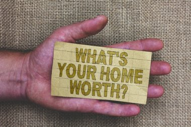 Conceptual hand writing showing What s is Your Home Worth question. Business photo showcasing Value of a house Property Cost Price Rate Thick gray paper with words human hands jute sack background