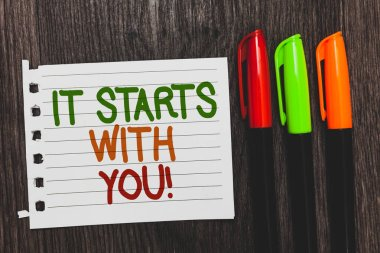 Handwriting text It Starts With You. Concept meaning Motivation for starting doing something Have discipline Colorful words with white page red green orange pen on blackish wooden desk