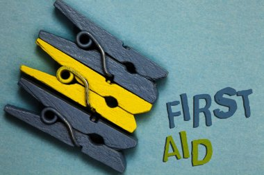 Conceptual hand writing showing First Aid. Business photo text Practise of healing small cuts that no need for medical training Gray yellow vintage clothespins clear background Holding things