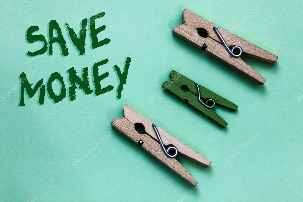 Text sign showing Save Money. Conceptual photo store some of your cash every month to use them sometime later Three brown green vintage clothespins clear background Holding things.