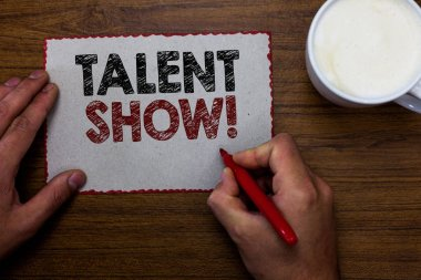 Word writing text Talent Show. Business concept for Competition of entertainers show casting their performances Man holding marker communicating ideas piece paper wooden table cup coffee.