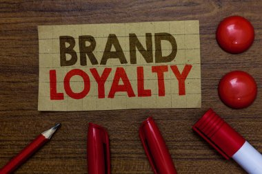 Handwriting text writing Brand Loyalty. Concept meaning Repeat Purchase Ambassador Patronage Favorite Trusted Paperboard markers pencil wooden background communicating ideas red balls.