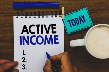 Conceptual hand writing showing Active Income. Business photo text Royalties Salaries Pensions Financial Investments Tips Man holding marker notebook clothepin reminder wooden table coffee.