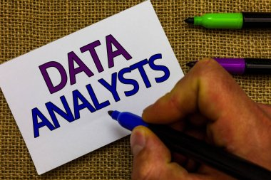 Text sign showing Data Analysts. Conceptual photo Programmer Design and Create Report Identifies patterns Man hand holding marker white paper communicating ideas Jute background.