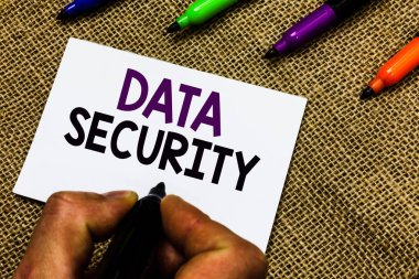 Writing note showing Data Security. Business photo showcasing Confidentiality Disk Encryption Backups Password Shielding Man hand holding marker white paper communicating idea Jute background.