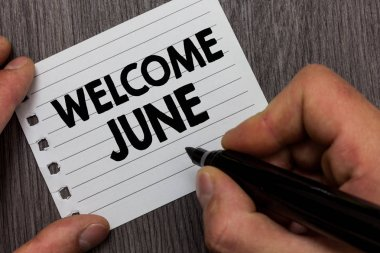Conceptual hand writing showing Welcome June. Business photo showcasing Calendar Sixth Month Second Quarter Thirty days Greetings Man holding marker notebook page Wooden background.
