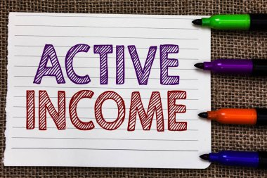Conceptual hand writing showing Active Income. Business photo showcasing Royalties Salaries Pensions Financial Investments Tips Notebook Paper Important reminder Markers Jute background.