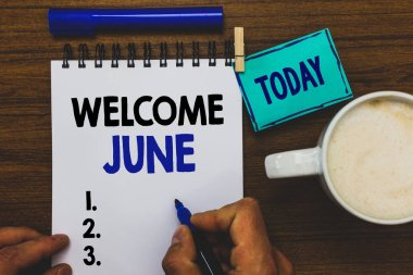 Conceptual hand writing showing Welcome June. Business photo text Calendar Sixth Month Second Quarter Thirty days Greetings Man holding marker notebook clothepin reminder wooden table coffee.