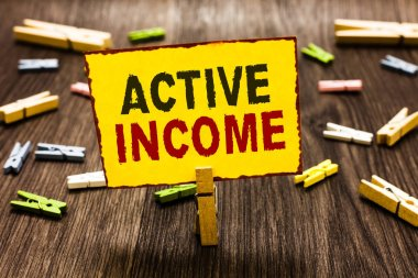 Handwriting text writing Active Income. Concept meaning Royalties Salaries Pensions Financial Investments Tips Clothespin holding yellow paper note several clothespins wooden floor.