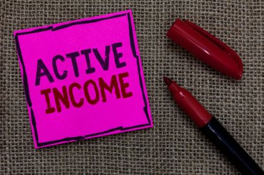 Word writing text Active Income. Business concept for Royalties Salaries Pensions Financial Investments Tips Pink paper Important reminder Marker Communicate ideas Jute background.